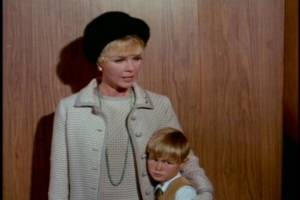 In the elevator, they encounter a sad-looking boy clutched protectively by his mother.
